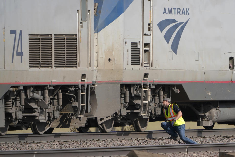 A worker peers under an Amtrak train engine, Sunday, Sept. 26, 2021, that was part of a train that derailed Saturday just west of Joplin, Mont. The westbound Empire Builder was en route to Seattle from Chicago, with two locomotives and 10 cars. (AP Photo/Ted S. Warren)