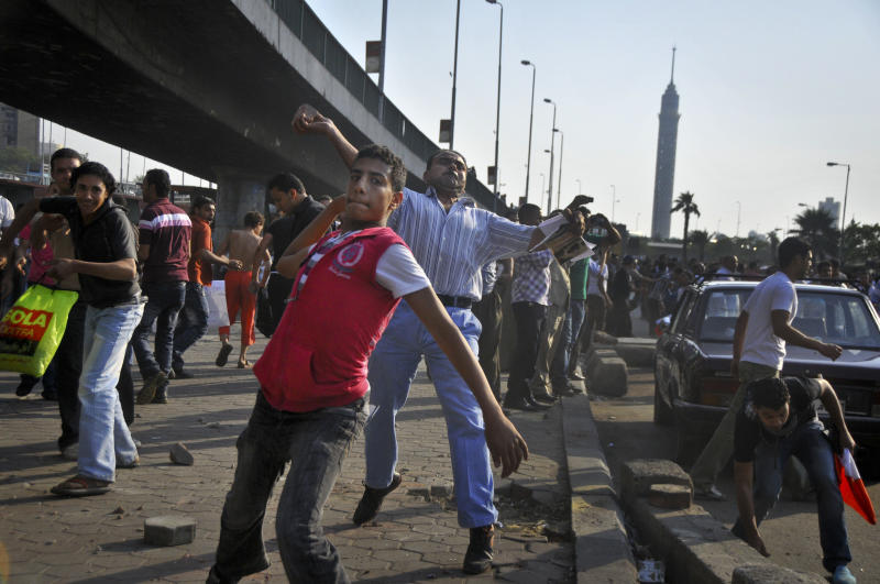 Some hundreds of Christians and Muslims hurl stones at each other during clashes near the Corniche in Cairo, Egypt Sunday, May 8, 2011.  The clashes on Sunday come hours after ultraconservative Muslim mobs set fire overnight to a church and a Christian-owned apartment building in a frenzy of violence that killed 12 people and injured more than 200. (AP Photo)