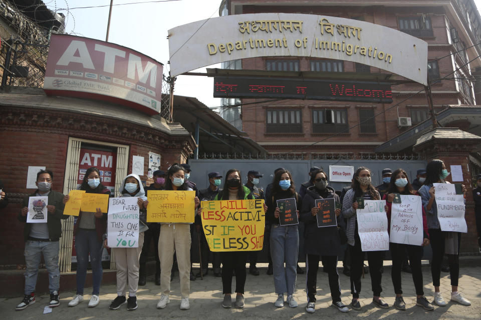 Nepalese women hold placards against a proposed rule which restricts foreign travel for women under 40 years during a protest outside the Department of Immigration in Kathmandu, Nepal, Thursday, Feb.11, 2021. Nepal government is proposing a new rule that says women under 40 years of age must seek consent from the family–and even the concerned ward office–to travel abroad on a visit visa. (AP Photo/Niranjan Shrestha)