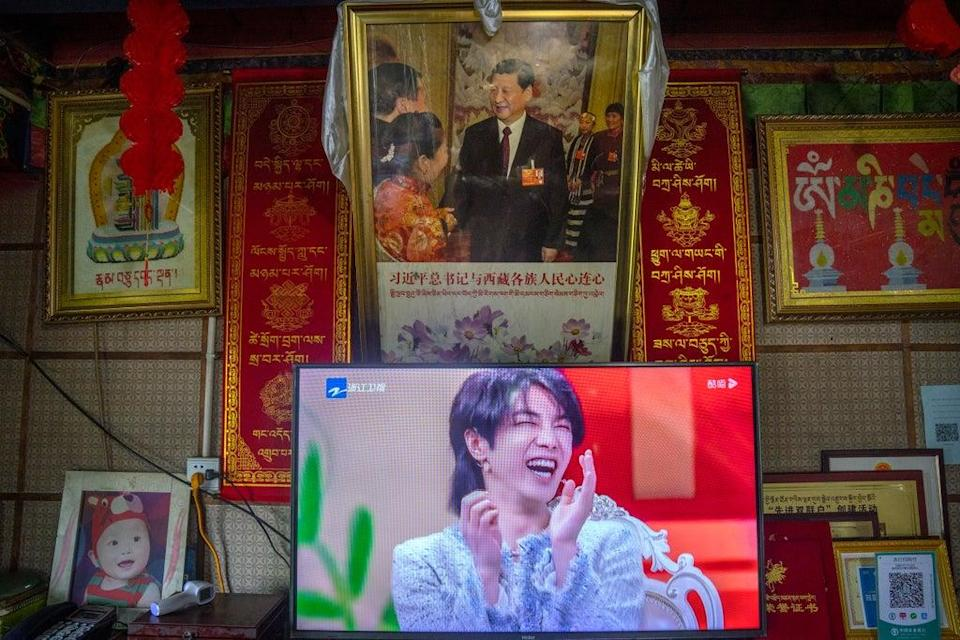 File: A television broadcast shows a Chinese talk show programme beneath a photo of Xi Jinping in western China   (AP)