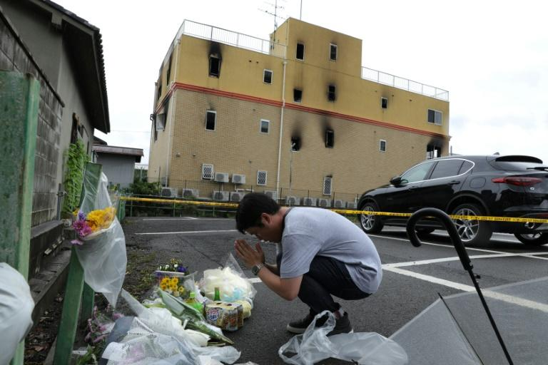 A man prays next to flowers and tributes laid at the scene where at least 34 people died in a suspected arson attack at an anime company in Kyoto, Japan