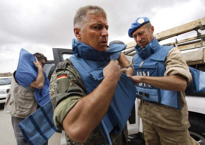 In this picture taken during a UN observer-organized tour, UN observers don body armor upon their arrival in Hama city, central Syria, on Thursday May 3, 2012. Syrian security forces stormed dorms at a northwestern university to break up anti-government protests there, killing at least four students and wounding several others with tear gas and live ammunition, activists and opposition groups said Thursday. (AP Photo/Muzaffar Salman)