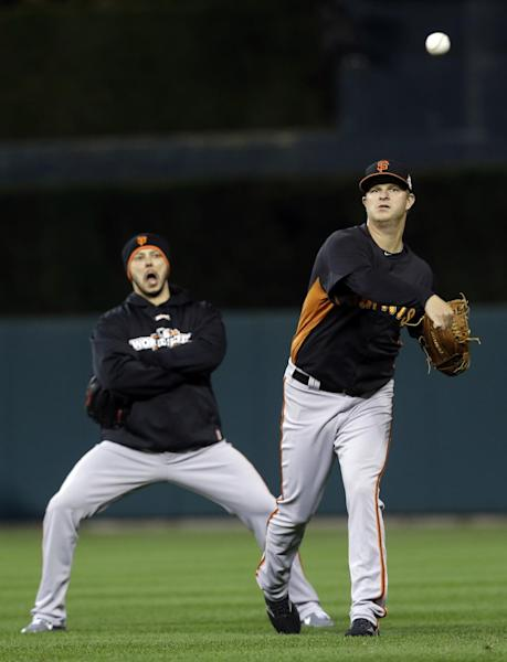 San Francisco Giants starting pitcher Matt Cain warms up as relief pitcher Clay Hensley, left, watches during a workout at Comerica Park in Detroit, Friday, Oct. 26, 2012. The Giants are scheduled to play the Detroit Tigers in Game 3 of baseball's World Series on Saturday in Detroit, with the Giants up 2-0. (AP Photo/Paul Sancya)
