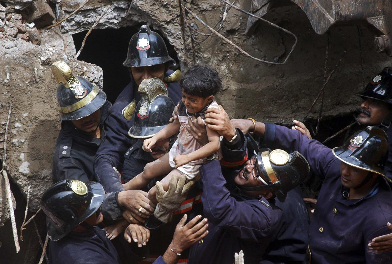 Rescue workers carry a girl who was rescued from the rubble at the site of a collapsed residential building in Mumbai September 27, 2013. The five-storey apartment block collapsed on Friday in the Indian financial centre of Mumbai, killing at least four people and trapping scores in the latest accident to underscore shoddy building standards in Asia's third-largest economy. REUTERS/Stringer (INDIA - Tags: DISASTER TPX IMAGES OF THE DAY)