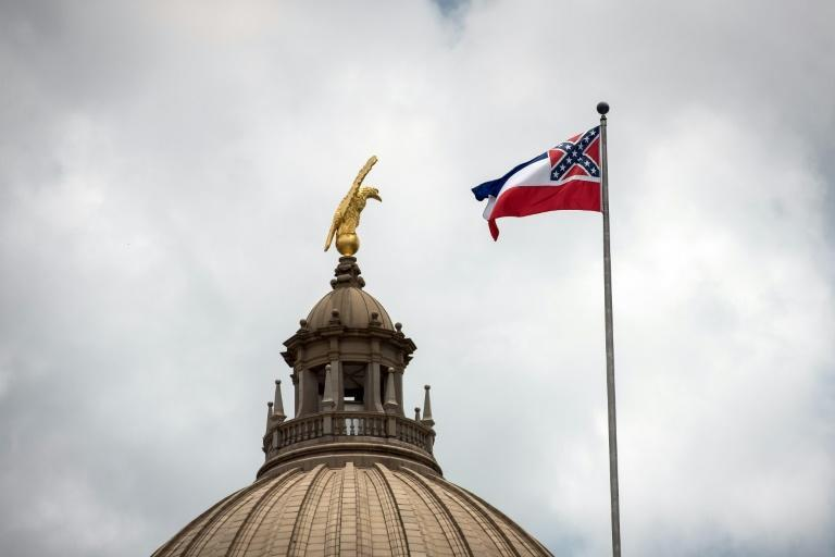 The state flag of Mississippi, which bears a Confederate emblem, is shown here flying over the capitol building in Jackson days before it was lowered and permanently retired on July 1, 2020 (AFP Photo/Rory Doyle)