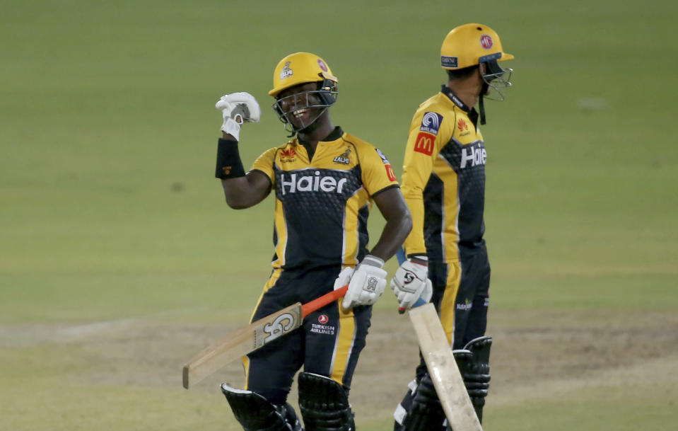 Peshawar Zalmi' Sherfane Rutherford, left, celebrates after playing winning shot during a Pakistan Super League T20 cricket match between Quetta Gladiators and Peshawar Zalmi at the National Stadium, in Karachi, Pakistan, Friday, Feb. 26, 2021. (AP Photo/Fareed Khan)