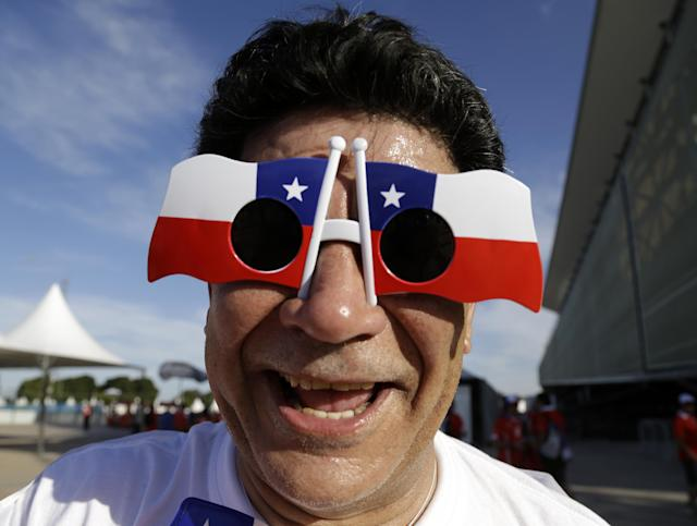 A Chile soccer fan poses for a photograph in his Chile flag glasses before the start of his team's World Cup match with Australia at the Arena Pantanal in Cuiaba, Brazil, Friday, June 13, 2014. (AP Photo/Thanassis Stavrakis)