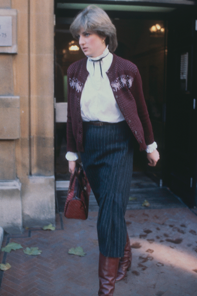 <p>Here's Diana leaving her flat at Earl's Court wearing a navy pinstripe skirt and an oxblood cardigan (with matching accessories) over a high-collar shirt, all tied together with a contrasting black bow.</p>