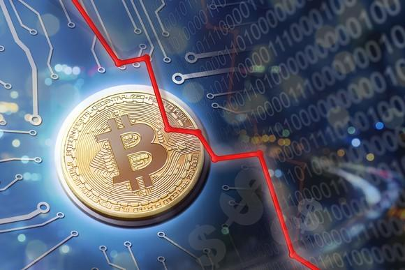A physical gold bitcoin surrounded by a plunging red line, circuitry, and binary code.