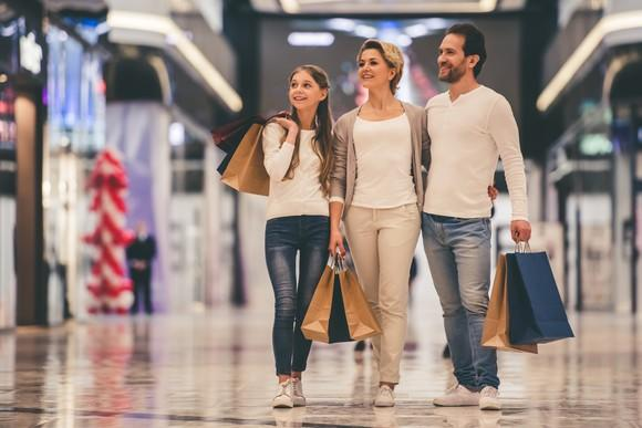 Family walking through a mall, carrying shopping bags.