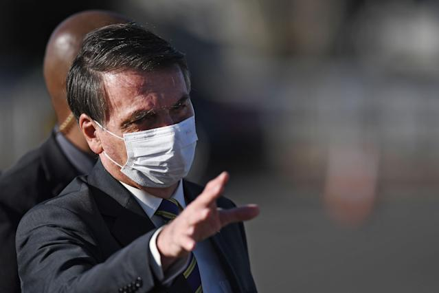 Brazilian President Jair Bolsonaro, wearing a face mask, waves to supporters as he arrives at the flag-raising ceremony before a ministerial meeting at the Alvorada Palace in Brasilia, on May 12, 2020, amid the new coronavirus pandemic. (Photo by EVARISTO SA / AFP) (Photo by EVARISTO SA/AFP via Getty Images)