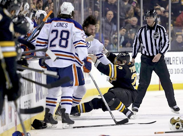 Edmonton Oilers left wing Luke Gazdic throws a punch as Boston Bruins right wing Shawn Thornton (22) falls to the ice during a fight in the first period of an NHL hockey game, Saturday, Feb. 1, 2014 in Boston. Looking on is Oilers right wing Ryan Jones (28). (AP Photo/Mary Schwalm)