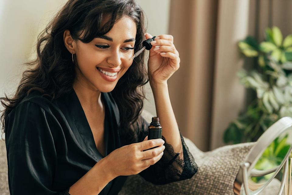 woman applying face serum from dropper