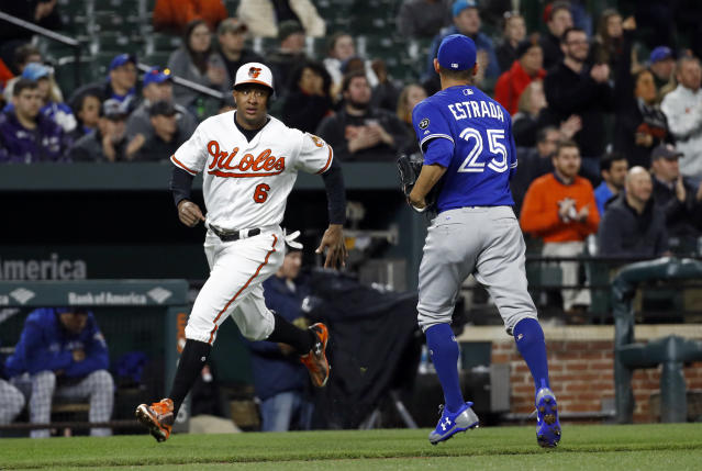 Baltimore Orioles' Jonathan Schoop, left, passes Toronto Blue Jays starting pitcher Marco Estrada on his way to home plate for a run on Chris Davis' single in the fourth inning of a baseball game, Wednesday, April 11, 2018, in Baltimore. (AP Photo/Patrick Semansky)