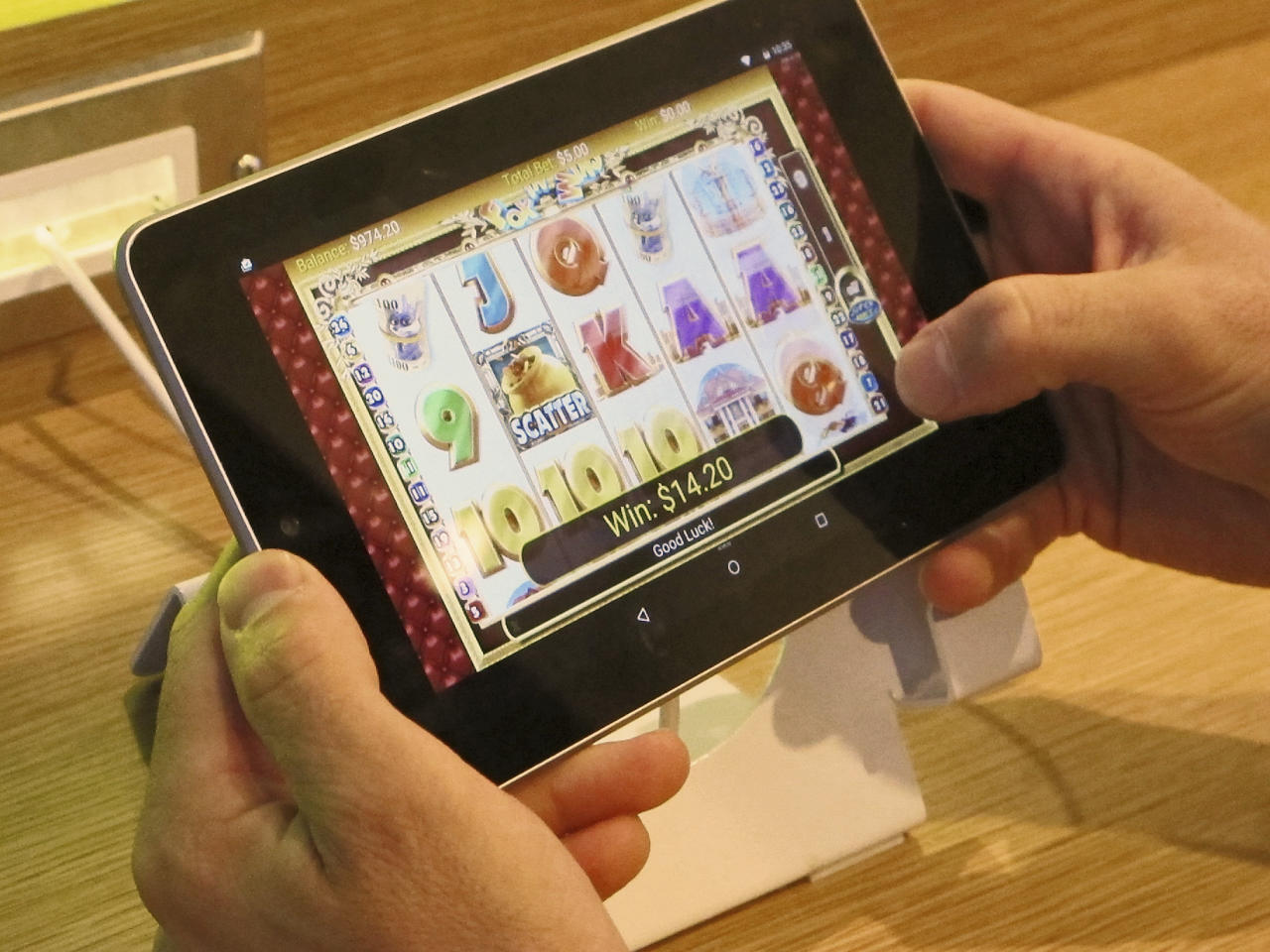 FILE – In this April 15, 2015, file photo, an employee at Resorts Casino Hotel tries a touchscreen tablet device the day before the opening of the casino's internet gambling lounge in Atlantic City, N.J. The U.S. Supreme Court is set to hear arguments Dec. 4, 2017, as the state of New Jersey challenges a 1992 law forbidding state-authorized sports gambling in all but four states that met a 1991 deadline to legalize it: Delaware, Montana, Nevada and Oregon. (AP Photo/Wayne Parry, File)