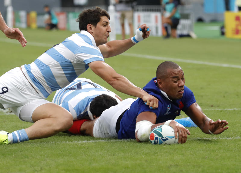 CORRECTS NAME OF SCORER : France's Gael Fickou, right, dives across the line to score a try during the Rugby World Cup Pool C game at Tokyo Stadium between France and Argentina in Tokyo, Japan, Saturday, Sept. 21, 2019. (AP Photo/Christophe Ena)