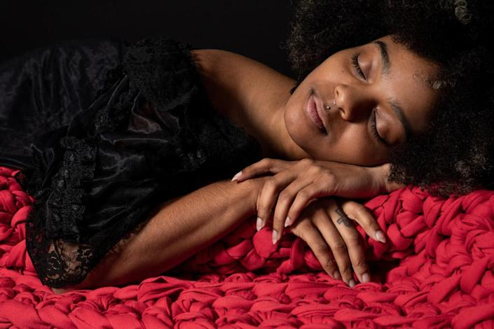 A photo of a model with a Sheltered Co. weighted blanket.