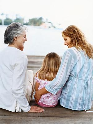 blonde girl sitting on dock with mother and grandmother
