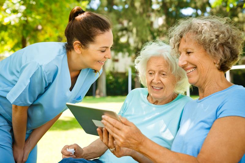 Smiling nurse looking at senior women using digital tablet. Healthcare worker is with retired females at nursing home. They are at back yard.