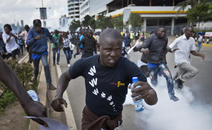 Opposition supporters flee from tear gas grenades fired by riot police during a protest in downtown Nairobi, Kenya Monday, May 16, 2016. Kenyan police have tear-gassed and beaten opposition supporters during a protest demanding the disbandment of the electoral authority over alleged bias and corruption. (AP Photo/Ben Curtis)