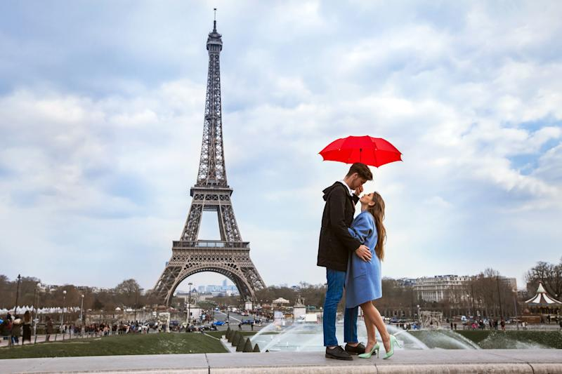 beautiful couple with umbrella near Eiffel Tower, honeymoon in Paris, romantic moment