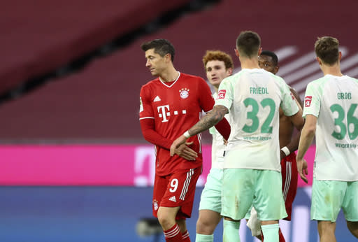 Bayern's Robert Lewandowski, left, and Bremen's Marco Friedl, second left, leave the field after the German Bundesliga soccer match between FC Bayern Munich and SV Werder Bremen in Munich, Germany, Saturday, Nov. 21, 2020. (AP Photo/Matthias Schrader)