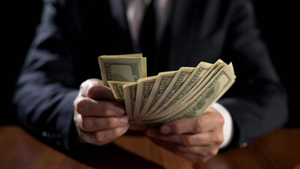 Corrupt official holding bundle of money, taking bribe for abuse of power