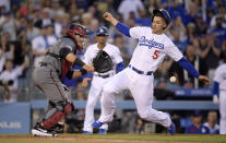 Los Angeles Dodgers' Corey Seager, right, scores on a single by Cody Bellinger as Arizona Diamondbacks catcher Alex Avila takes a late throw during the third inning of a baseball game Saturday, March 30, 2019, in Los Angeles. (AP Photo/Mark J. Terrill)
