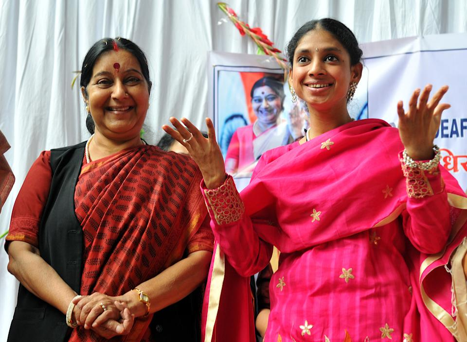 Geeta expresses herself through gestures as Sushma Swaraj looks on at Indore Deaf Bilingual Academy (IDBA) on November 23, 2015. (Photo by Shankar Mourya/Hindustan Times via Getty Images)