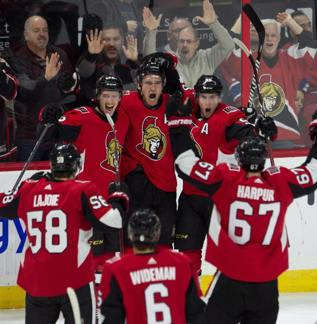 Ottawa Senators celebrate teammate Mark Stone's game-winning goal during overtime of an NHL game in Ottawa, Ontario, Saturday, Oct. 20, 2018. The Senators won, 4-3, in overtime. (Adrian Wyld/The Canadian Press via AP)