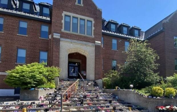 Algoma University in Sault Ste. Marie, Ont., is on the site where Shingwauk Indian Residential School was located. Shoes and flowers line the front steps in memory of an estimated 215 children whose remains were detected at a onetime residential school in Kamloops, B.C. (Algoma University - image credit)
