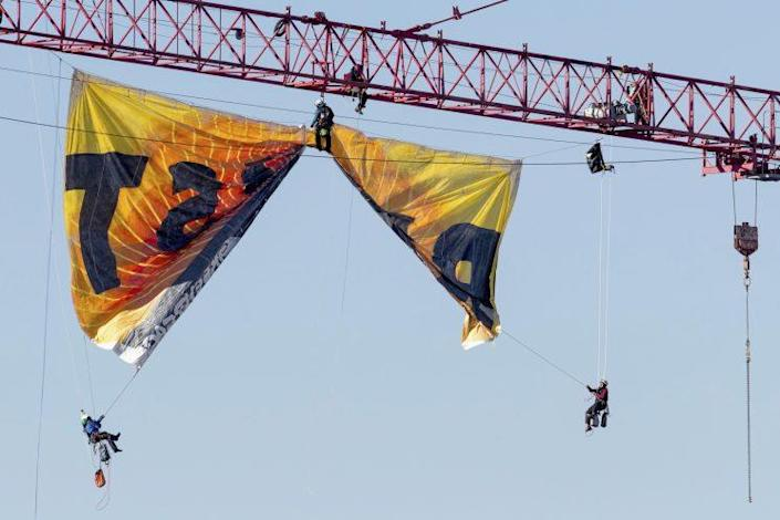 Greenpeace protesters unfurl a banner from a crane near the White House