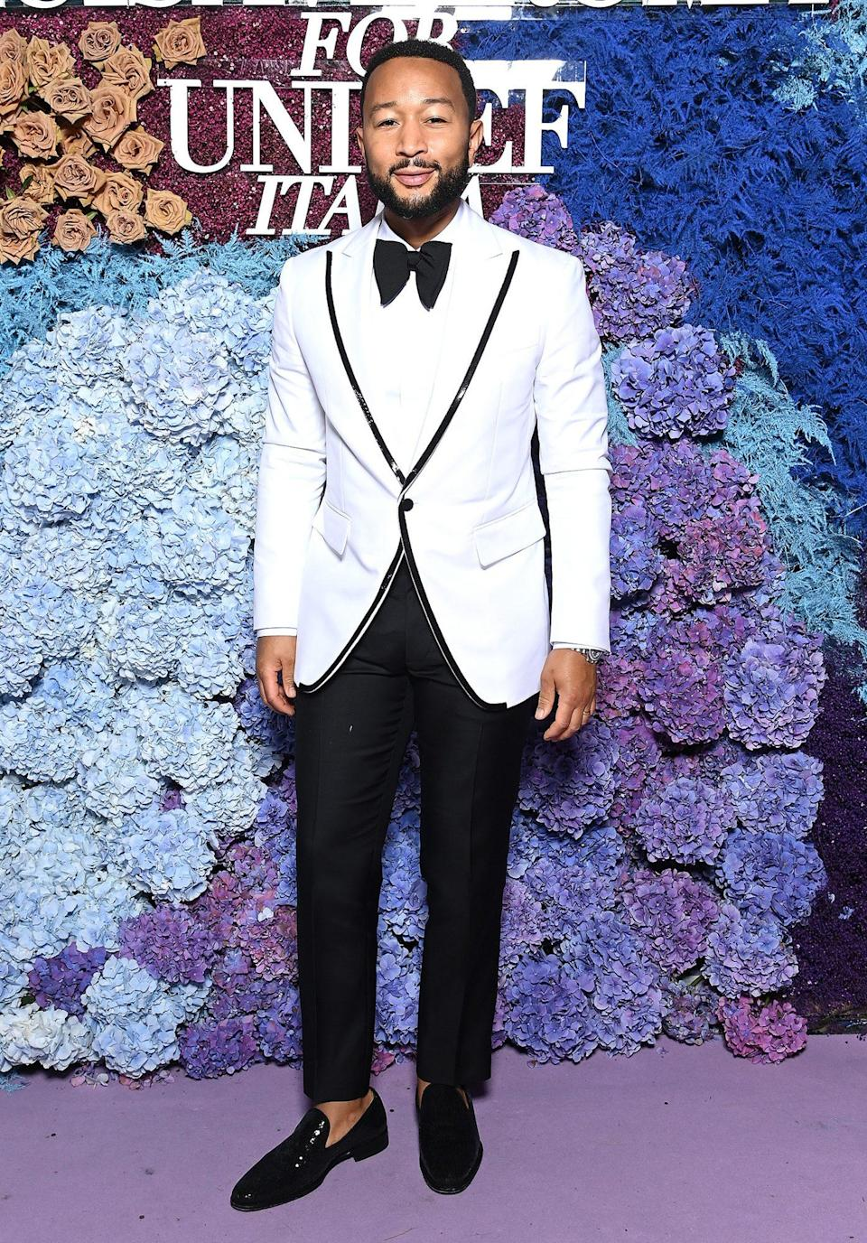 """<p>looks dapper in a white jacket with black piping, bow tie and loafers before <a href=""""https://people.com/music/katy-perry-john-legend-moon-river-duet-unicef-gala-italy/"""" rel=""""nofollow noopener"""" target=""""_blank"""" data-ylk=""""slk:hitting the stage to perform"""" class=""""link rapid-noclick-resp"""">hitting the stage to perform</a>.</p>"""