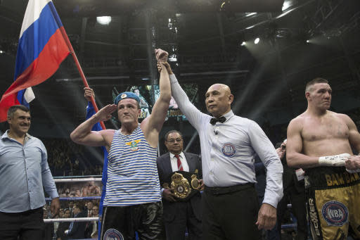 FILE - In this Sunday, July 9, 2017 file photo, Russian boxer Denis Lebedev, center left, celebrates his victory against Australian Mark Flanagan, right, after their cruiserweight WBA Super World title bout in Ekaterinburg, Russia. Former world cruiserweight boxing champion Denis Lebedev has retired aged 39 after a lengthy and colorful career, it was announced Thursday, July 11, 2019.(AP Photo/Anton Basanaev, File)