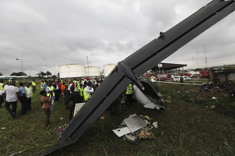 Rescue workers gather around the wreckage of a charter passenger jet which crashed soon after take off from Lagos airport, Nigeria, Thursday, Oct. 3, 2013. Officials said there were casualties but refused to confirm reports of several deaths. (AP Photo/Sunday Alamba)
