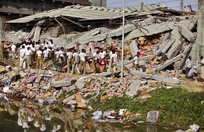 Indian rescue workers shift through the debris of a collapsed factory in Jalandhar, India, Monday, April 16, 2012. Several people are feared to be trapped after a three-story building of a factory collapsed after a blast in the factory's boiler, according to local reports. (AP Photo/Altaf Qadri)