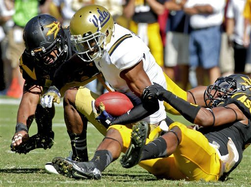 UCLA wide receiver Shaquelle Evans, center, is tackled by Arizona State safety Keelan Johnson, right, and linebacker Anthony Jones, left, during the first half of an NCAA College football game, Saturday, Oct. 27, 2012, in Tempe, Ariz. (AP Photo/Matt York)