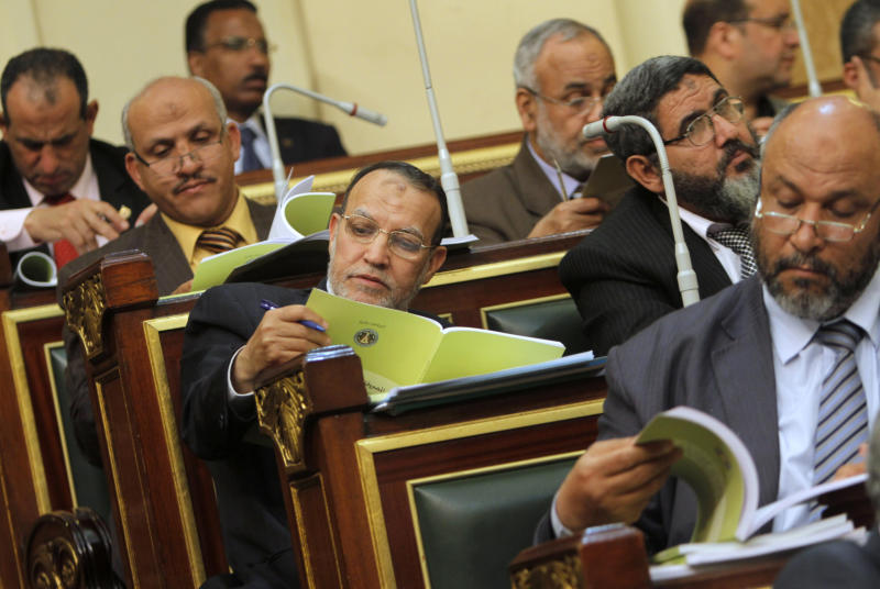 Egyptian Shura council member and vice president of the Muslim Brotherhood's Freedom and Justice Party Essam el-Erian, center, reads the government's 2013-2014 budget at the Shura Council, Parliament's upper house, Tuesday, April 23, 2013. (AP Photo/Amr Nabil)