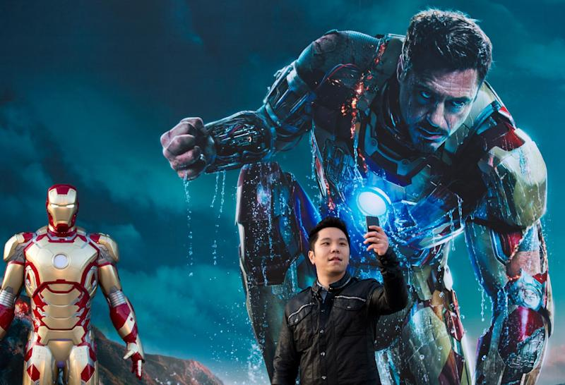"FILE - In this April 6, 2013 file photo, a Chinese man uses a smartphone to take his own photo with an ""Iron Man"" poster together with a costumed figure, left, during a promotional event of the new movie ""Iron Man 3"" at the Imperial Ancestral Temple in Beijing's Forbidden City. From demanding changes in plot lines that denigrate the Chinese leadership, to dampening lurid depictions of sex and violence, Beijing is having increasing success in pressuring Hollywood into deleting movie content Beijing finds objectionable. It's even getting American studios to sanction alternative versions of films specially tailored for Chinese audiences, like ""Iron Man 3,"" which debuts in theaters around the world later this week. The Chinese version features local heartthrob Fan Bingbing - absent from the version showing abroad - and lengthy clips of Chinese scenery that local audiences love. (AP Photo/Andy Wong, File)"
