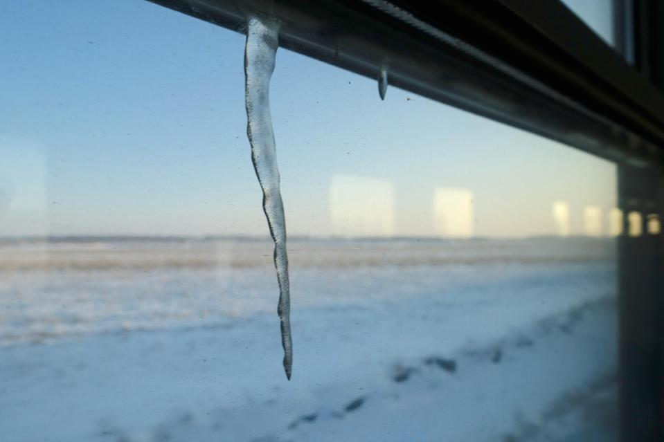 cicle hangs off the window frame on a train heading to the coal-producing city of Hegang