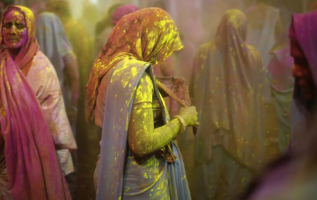 Women, who are former scavengers, are daubed in colours as they take part in Holi celebrations organised by non-governmental organisation Sulabh International at a widow's ashram in Vrindavan in the northern Indian state of Uttar Pradesh March 14, 2014. Holi, also known as the Festival of Colours, heralds the beginning of spring and is celebrated all over India. REUTERS/Ahmad Masood (INDIA - Tags: SOCIETY RELIGION)