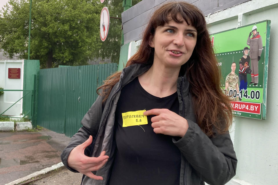 FILE - In this Wednesday, May 19, 2021 file photo, Belarusian journalist Katsiaryna Barysevich, who was sentenced to six months over her investigation into a protester's death, shows her yellow prison's label to colleagues upon her release from the prison in Komarovka, Belarus. Political prisoners in Belarus are coming under increasing pressure following the recent arrest of activist Raman Pratasevich from a forcibly diverted Ryanair flight. Human rights groups say these prisoners have been marked with yellow tags sewn into their prison uniforms to single them out from regular prisoners. (AP Photo)