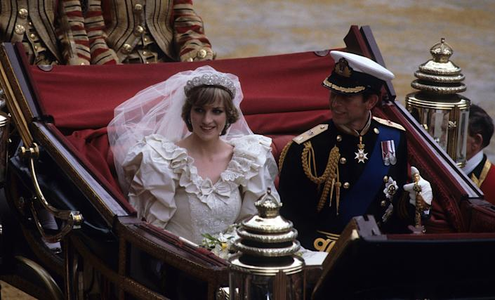 LONDON, ENGLAND - JULY 29: Prince Charles, Prince of Wales and Diana, Princess of Wales, wearing a wedding dress designed by David and Elizabeth Emanuel and the Spencer family Tiara, ride in an open carriage, from St. Paul's Cathedral to Buckingham Palace, following their wedding on July 29, 1981 in London, England. (Photo by Anwar Hussein/Getty Images)