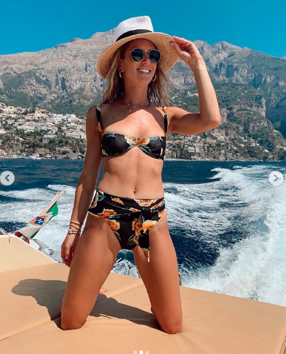 Marissa Casey Grossman poses on a boat in a floral black bikini with hat and sunglasses in Capri Italy