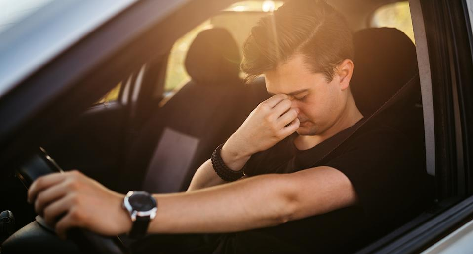A young man looking sad in his car. Source: Getty Images