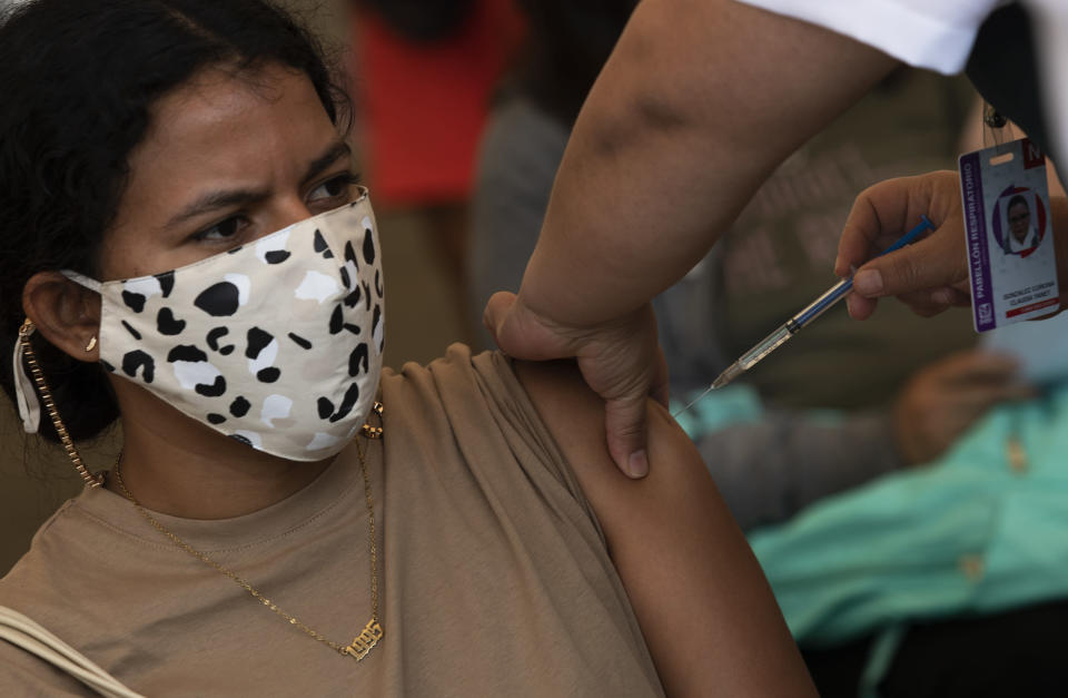 A healthcare worker injects a teacher with a dose of the CanSino COVID-19 vaccine, on the grounds of the National Polytechnic Institute, in Mexico City, Tuesday, May 18, 2021. Mexico is mounting a final push to get all of the country's school teachers vaccinated so that it can reopen schools, perhaps by June. (AP Photo/Marco Ugarte)