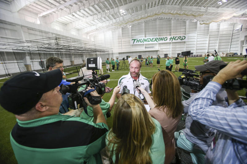 In this Sept. 6, 2014 photo, Chris Cline speaks with media as Marshall University dedicates the new indoor practice facility as the Chris Cline Athletic Complex in Huntington, W.Va. Police in the Bahamas say a helicopter flying from Big Grand Cay island to Fort Lauderdale has crashed, killing seven Americans on board. None of the bodies recovered from the downed helicopter have been identified, but police Supt. Shanta Knowles told The Associated Press on Friday, July 5, 2019, that the missing-aircraft report from Florida said billionaire Chris Cline was on board. (Sholten Singer/The Herald-Dispatch via AP)