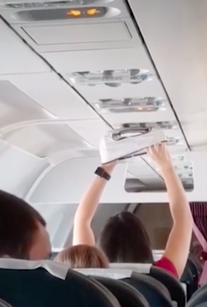 An unnamed woman spent 20 minutes drying a pair of underpants using the air vent over her head. Source: screenshot