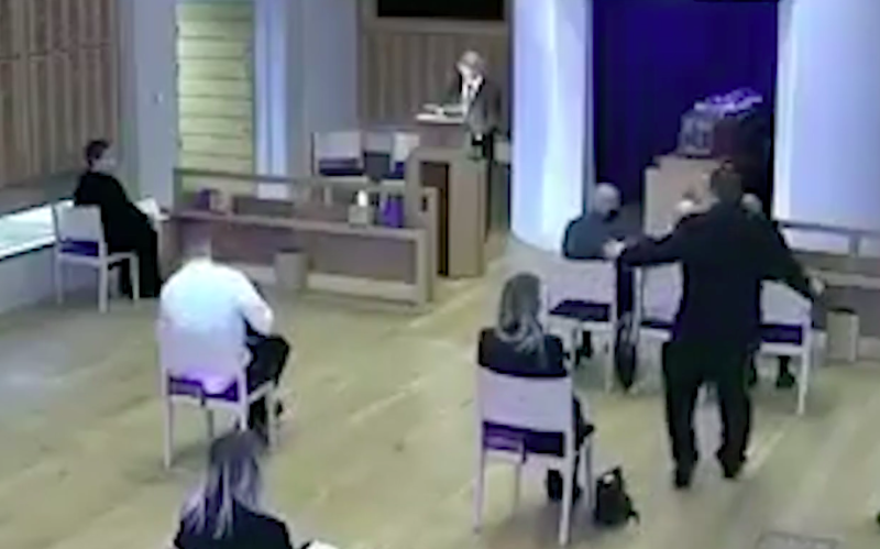 A staff member, standing, tells mourners not to sit together. (Milton Keynes Community Hub)