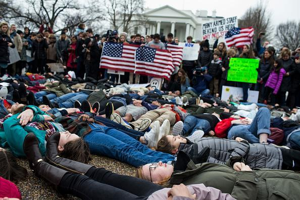 Demonstrators lie on the ground during a 'lie-in' demonstration supporting gun control reform near the White House on Feb.19, 2018 in Washington, DC. (Photo by Zach Gibson/Getty Images)